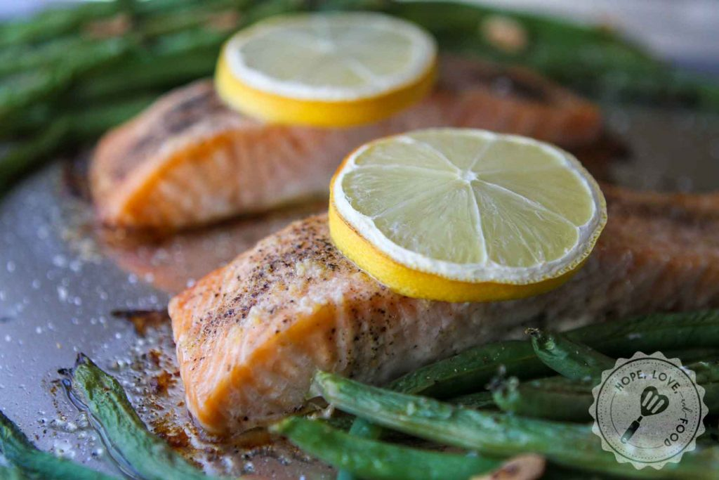 Two portions of salmon with lemon and green beans on a sheet pan.