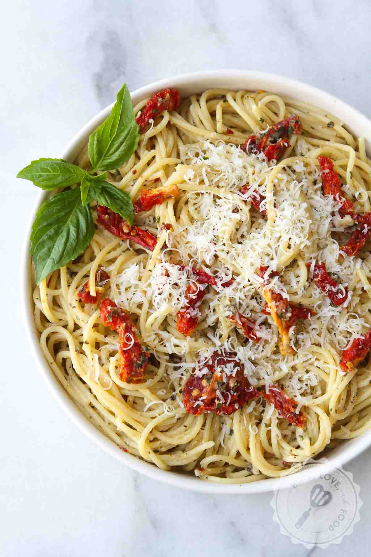 Garlic pasta with sun-dried tomatoes on a plate.