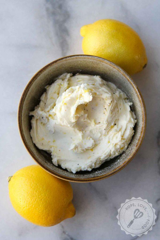 Lemon butter next to two lemons.